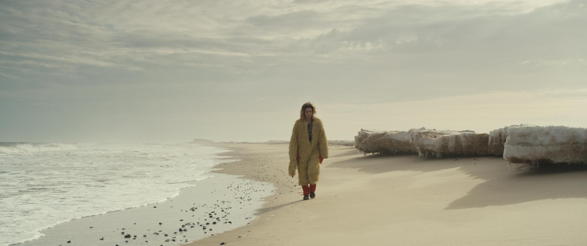 Éli marche sur une plage, dans un déguisement de poulet.
