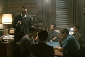 Un groupe de jeunes hommes assis à table discutent.