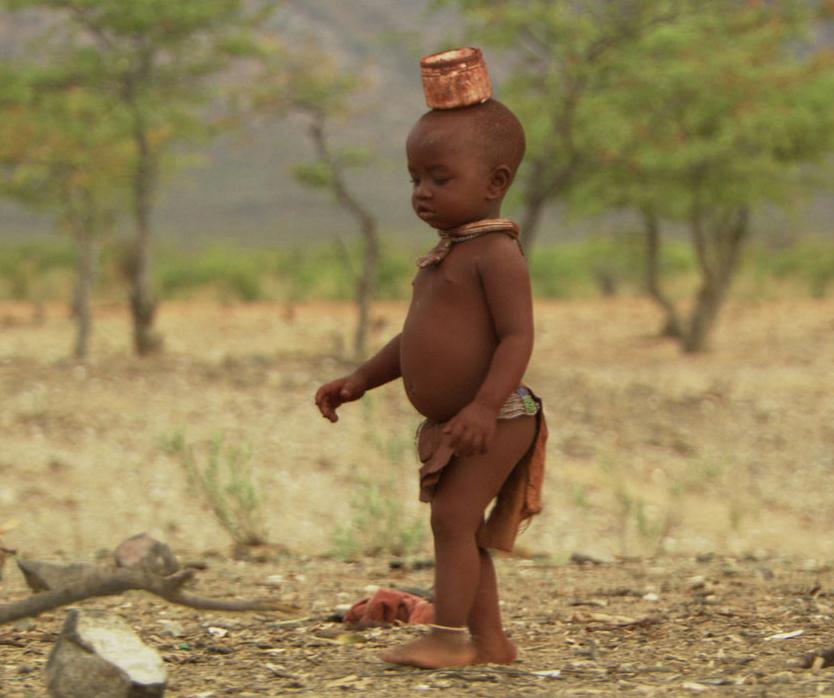 En Namibie, bébé Ponijao marche  avec un objet sur la tête.