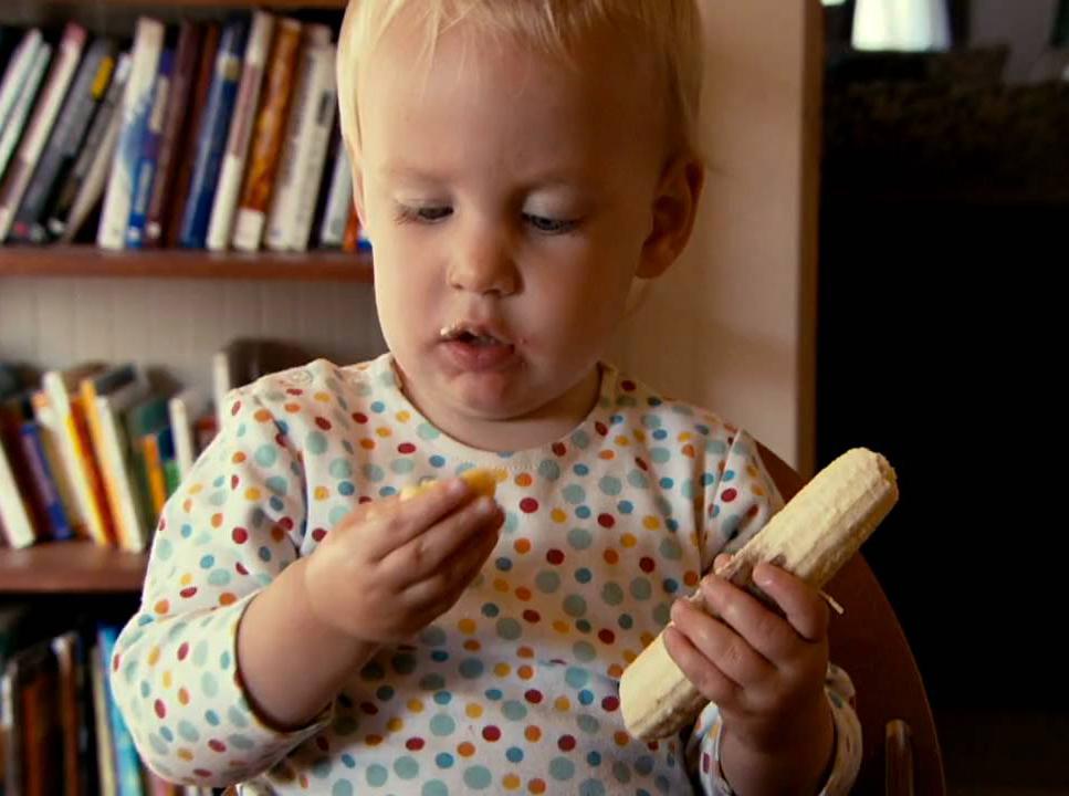 Aux États-Unis, bébé Hattie mange une banane.