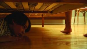 Le garçon caché sous le lit dans Les Démons.