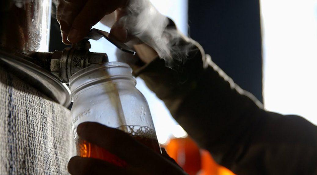 Du sirop fumant est vidé dans un contenant, dans Le goût d'un pays