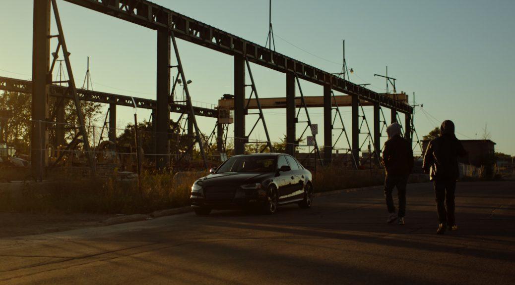 Hakeem et A-Mac marchent vers la voiture volée qu'ils doivent livrer, dans Boost.