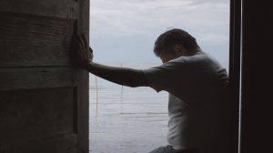 Le personnage découragé devant la montée des eaux, dans Gods Acre