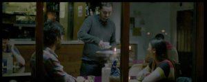 Richard et l'interprète Vann dans un café, vus de l'extérieur, dans Lilting
