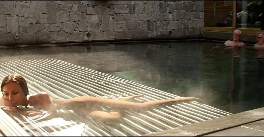 Jeune femme nue allongée dans l'eau avec les deux hommes âgés qui la regardent.