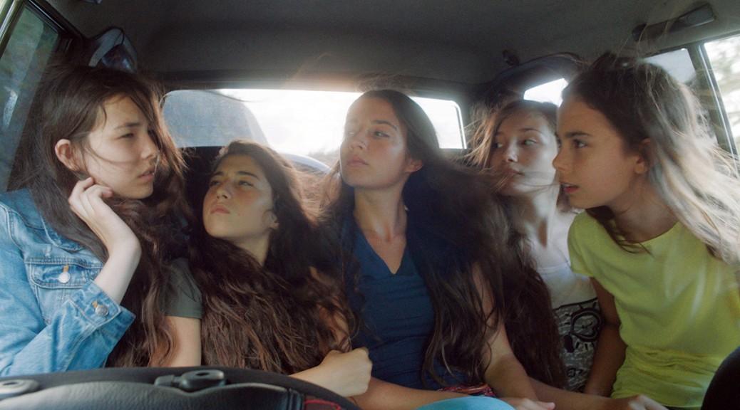 Les cinq soeurs assises dans une voiture.