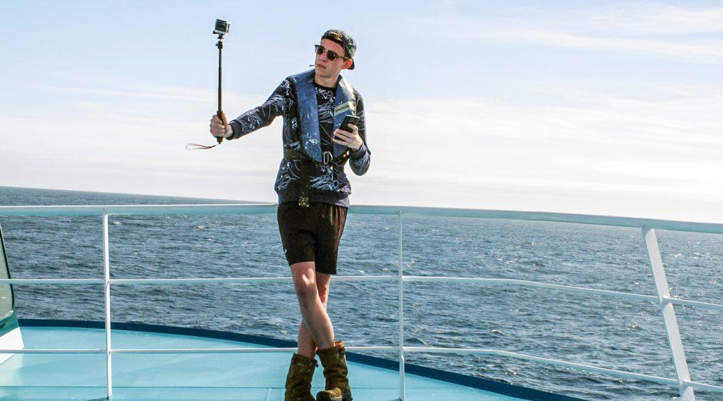 Un marin fait un selfie sur le pont du navire, dans Les terres lointaines