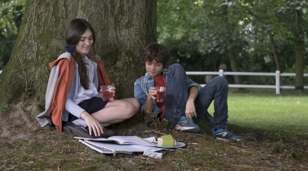 Marie et Victor étudient, assis dans l'herbe, dans Le coeur en braille