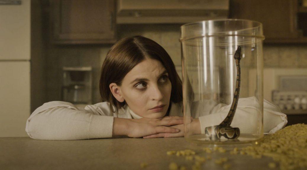 La peau sauvage - La jeune femme observe le python dans un bocal